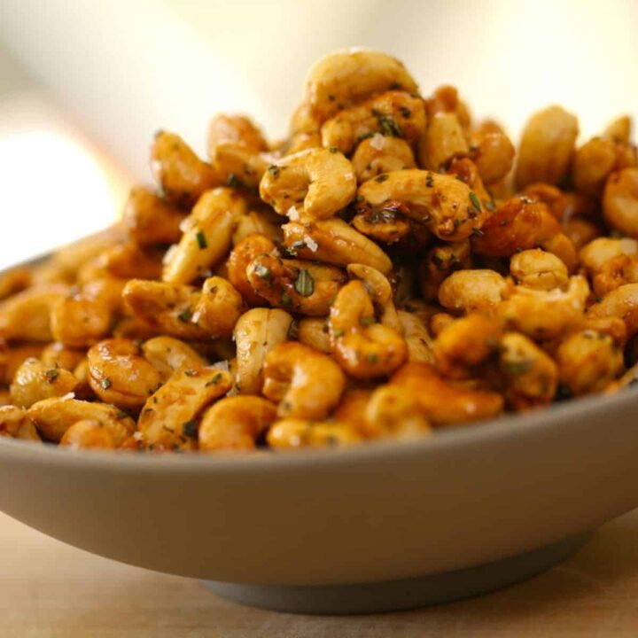 Honey Cashews with Rosemary Garnish in a Gray Bowl