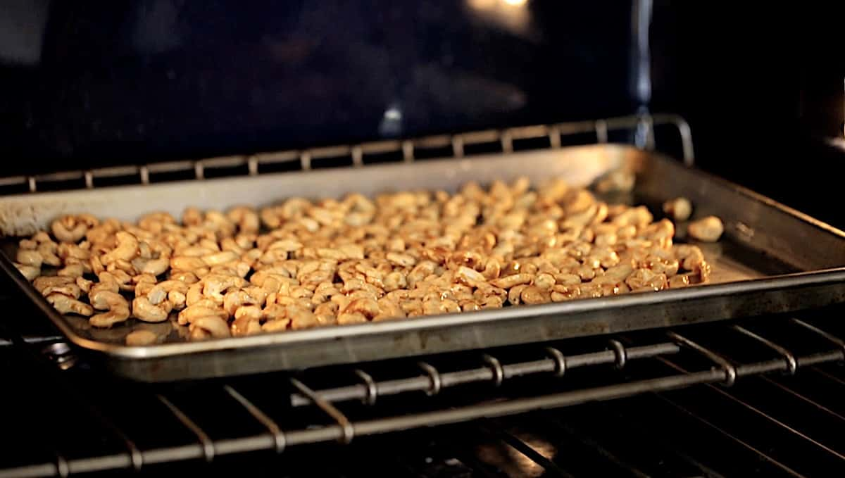 cashews on a sheet pan baking in the oven