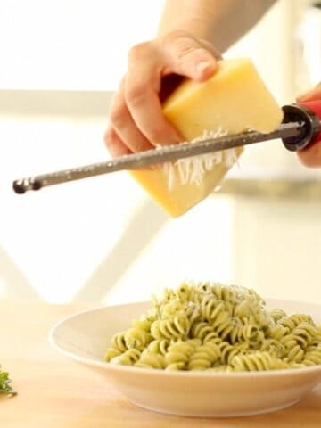 A person grating Cheese on top of pesto pasta