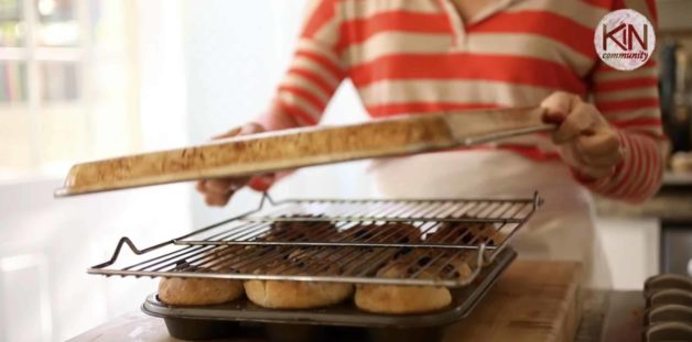 cookie sheet being placed on top of sticky buns before flipping them