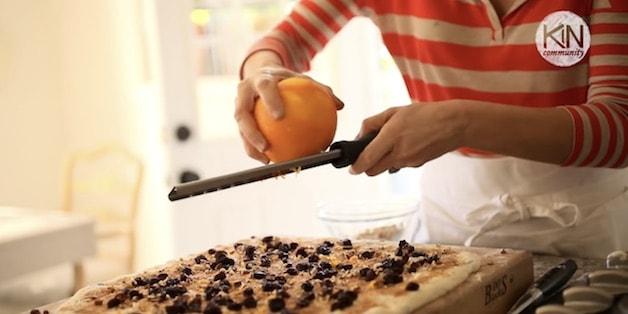 Grating orange zest on top of filling for sticky bun recipe.