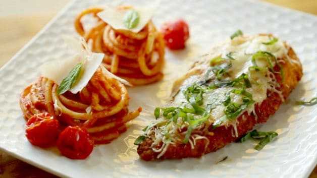 Chicken parmesan and pasta on a white plate
