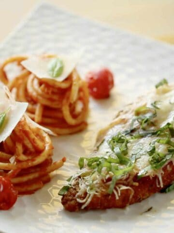 Finished plate of chicken parmesan and pasta mounds garnished with parmesan and fresh basil