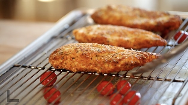 Fried chicken cutlets resting on a baking sheet with a roasting rack