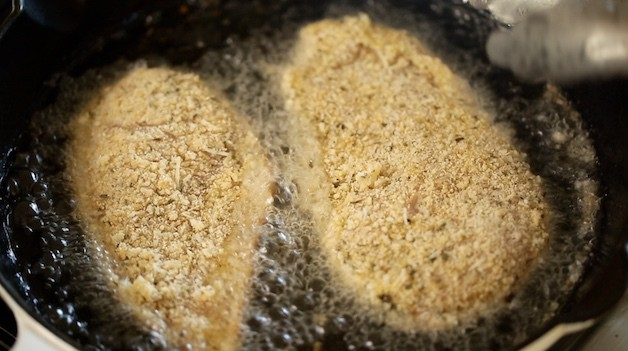 Breaded chicken cutlets frying in oil