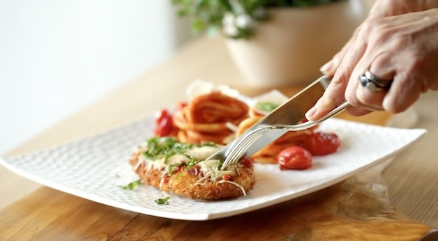 Fork and knife cutting into a chicken parmesan on a white plate