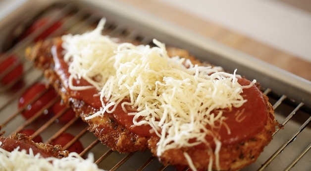 Tight shot of shredded mozzarella cheese on a breaded chicken cutlet with tomato sauce