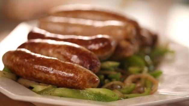 Sausages on bed of green peppers and onions