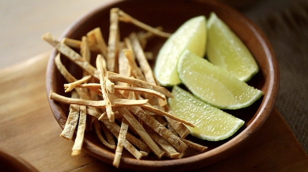 Terra cotta bowl filled with lime wedges and tortilla strips