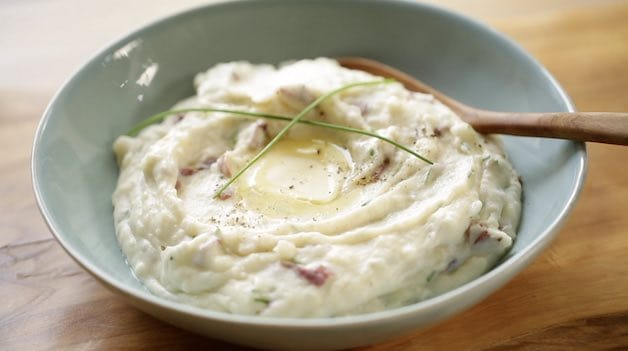 Bowl of mashed potatoes with melting butter, pepper and fresh chives