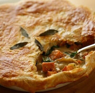 Pot pie with serving cut out of it with silver serving spoon