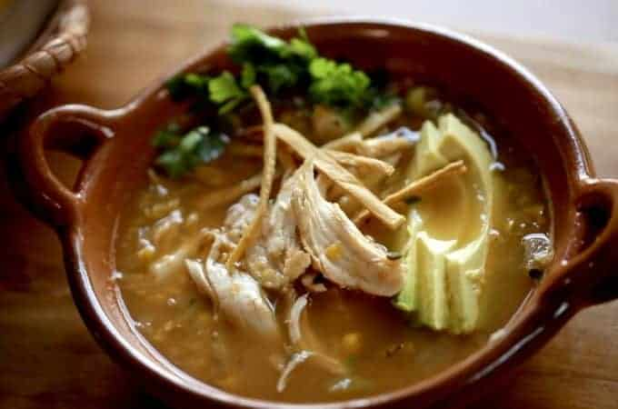 Easy White Chicken Chili Recipe served in a terra cota bowl topped with avocado and tortilla strips