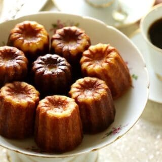 Caneles in a Floral Serving Dish with a cup of coffee in background