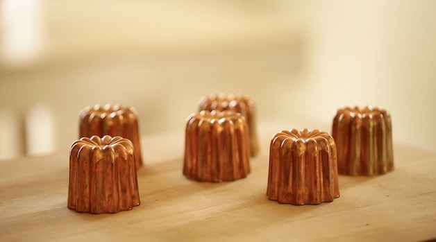 a selection of copper canele molds on a cutting board