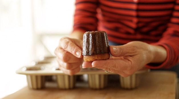 Holding up a freshly baked canele that is beautifully caramelized with a hard exterior