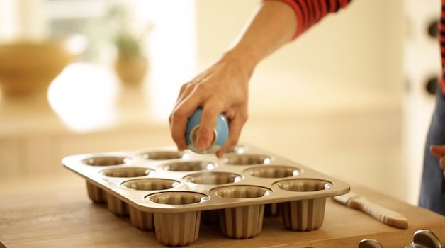Spraying a canele pan with baking spray
