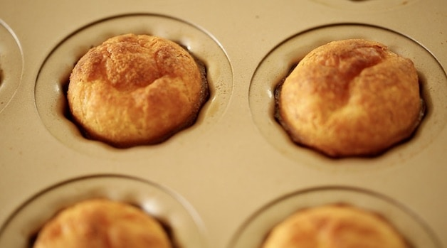 The golden brown tops of fresh caneles in a baking mold