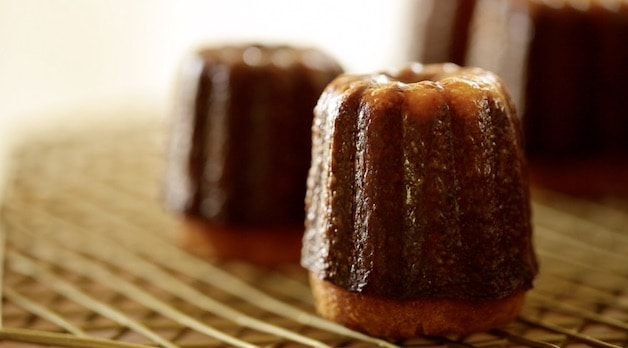 Two Caneles cooling on a cooling rack
