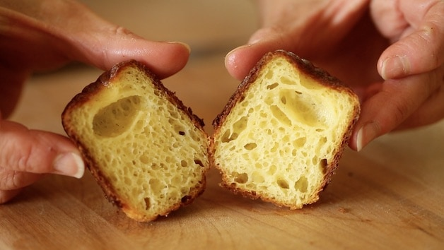 a canele cut in half showing the custardy interior texture