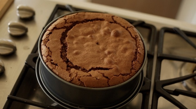 Overhead shot of a flourless chocolate cake on a cooktop