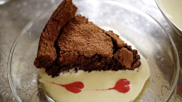 A slice of Flourless Chocolate Cake in a pool of creme anglaise with raspberry coulis hearts