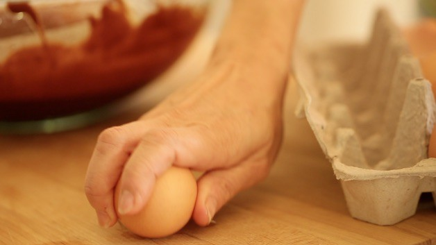 Cracking an egg on a wooden cutting board