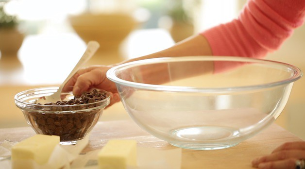 Clear bowl with chocolate chips and butter on a cutting board