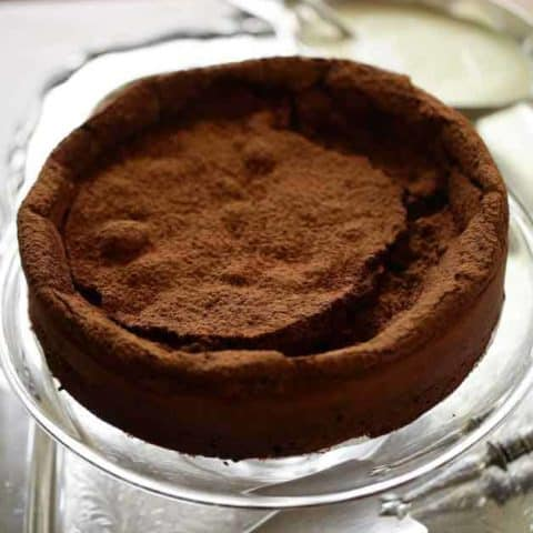 Vertical image of a flourless chocolate cake on a silver tray with silver cake server