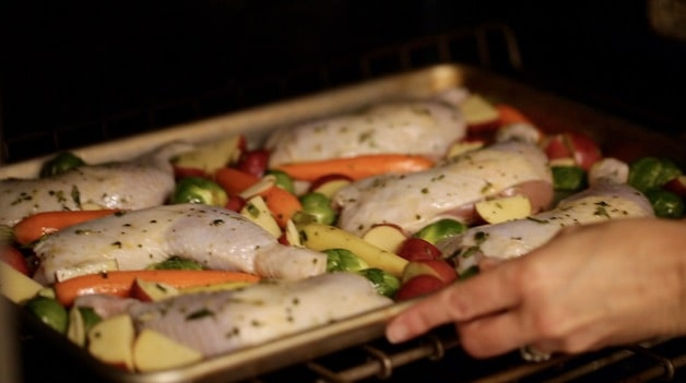 sheet pan chicken with potatoes and veggies going into the oven to bake