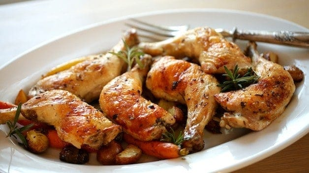 Roasted Chicken Legs on a platter with Potatoes and Veggies
