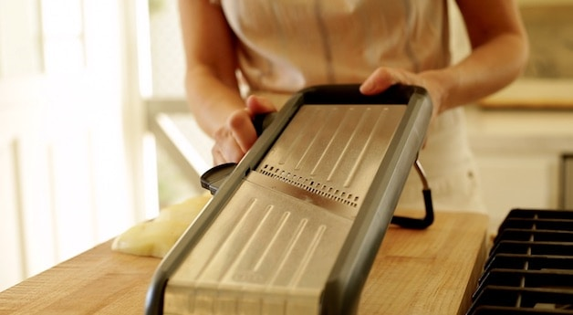 A person setting the thickness of a mandoline slicer