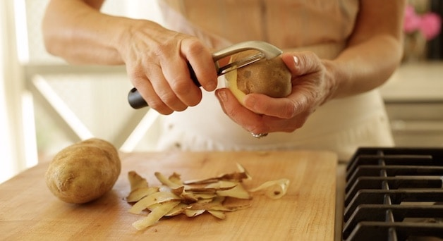 peeling a russet potato with a potato peeler over a cutting board