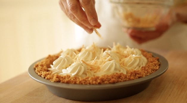 Coconut Cream Pie Recipe being topped with toasted coconut