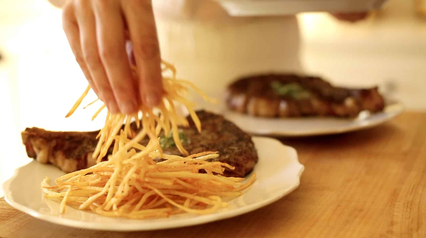a hand placing a mound of fried french fries on a plate next to a rib-eye steak topped with herb butter