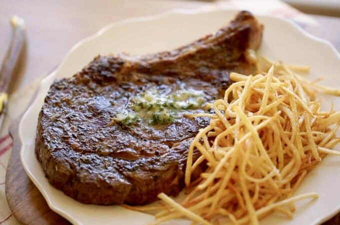 A rib-eye steak with Herb Butter on top and match stick French fries