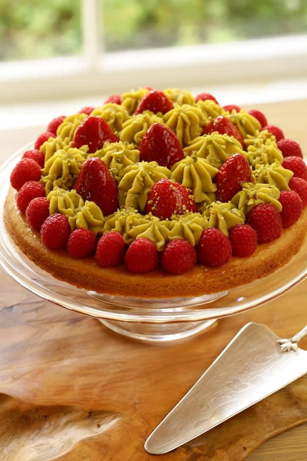 Strawberry Pistachio tart on a cake stand with silver server