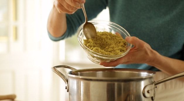adding pistachio paste to a sauce pot