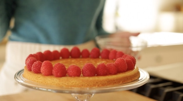 placing raspberries on a Strawberry Pistachio tart