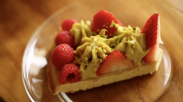 a slice of Strawberry Pistachio tart on a glass plate