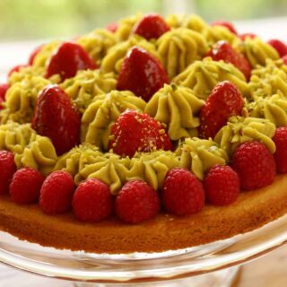 Strawberry Pistachio tart on a glass cake stand