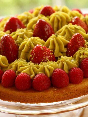Strawberry Pistachio tart on a glass cake stand