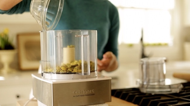 adding sugar to a food processor with pistachios in it