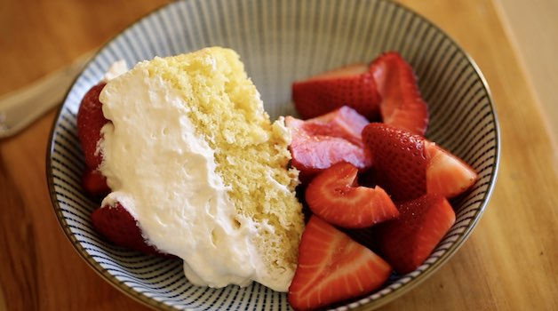 a slice of strawberry shortcake cheater charlotte on a blue plate with extra strawberries