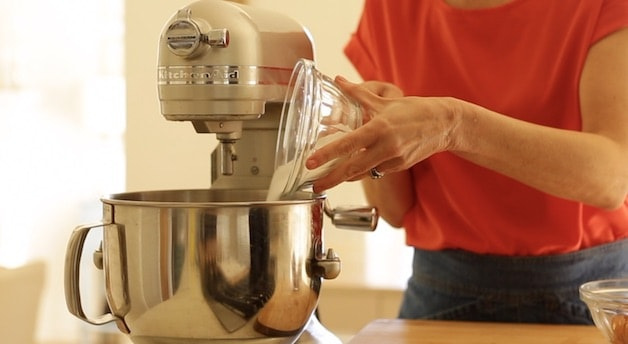 pouring sugar into a standing mixer