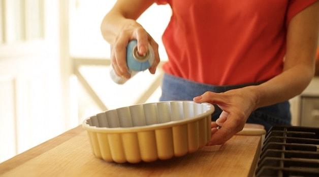 Spraying Charlotte pan with baking spray