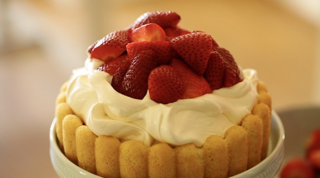 Strawberries piled on whipped cream and cake base