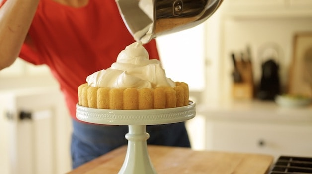 Pouring whipped cream into a sponge cake base