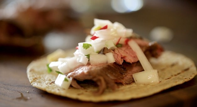 a fully assembled flank steak taco with Onion and Radish relish on a tortilla