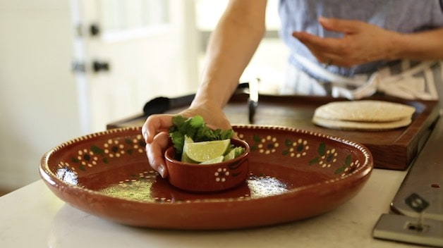 Placing a small bowl of limes and cilantro on a large Mexican Platter