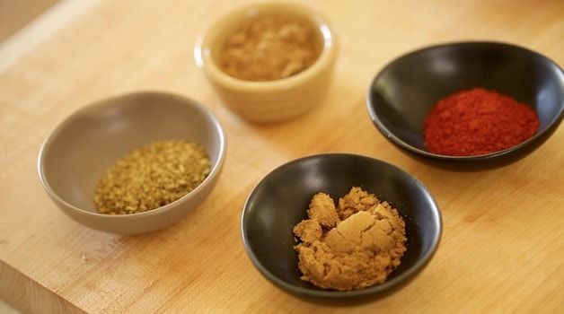a selection of ground spices in small bowls for a carne asada marinade